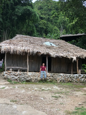 In front of a traditional bamboo Hmong house